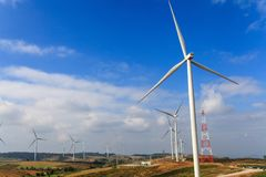 As turbinas eólicas gerenciem a eletricidade nas montanhas e no céu azul fotografia de stock