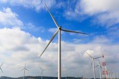 As turbinas eólicas gerenciem a eletricidade nas montanhas e no céu azul e branco imagens de stock