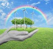 As turbinas eólicas, a grama e as árvores no ser humano cedem a grama verde w foto de stock