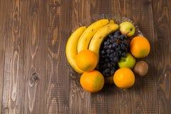 As uvas, as laranjas, as bananas, o quivi e as maçãs estão no prato Fotos de Stock Royalty Free