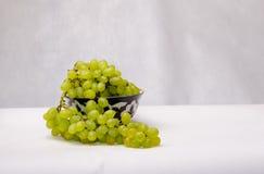 As uvas brancas frescas em uma turquesa decorada rolam em uma parte traseira do branco Fotos de Stock