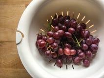 As uvas roxas dispararam usando a luz natural em uma tabela de madeira imagem de stock