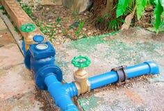 As válvulas molham o bronze com verde do botão no azul de aço da pintura da tubulação velha da junção da conexão no assoalho do c imagem de stock royalty free