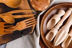 As várias colheres, colheres e forquilhas, placas e placas da cozinha são feitas da madeira Fotos de Stock
