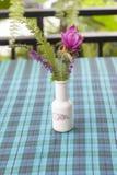 As várias flores no vaso são ficadas situadas na toalha de mesa fotografia de stock