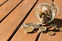 As várias moedas são dispersadas em uma tabela de madeira O conceito da pobreza foto de stock