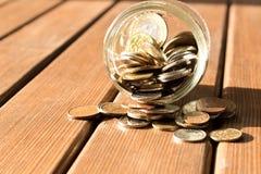 As várias moedas são dispersadas em uma tabela de madeira O conceito da pobreza imagens de stock royalty free