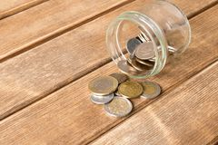 As várias moedas são dispersadas em uma tabela de madeira O conceito do po fotografia de stock