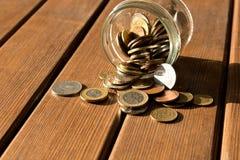 As várias moedas são dispersadas em uma tabela de madeira O conceito do po fotografia de stock royalty free