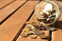 As várias moedas são dispersadas em uma tabela de madeira O conceito do po fotos de stock