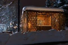 As van een boom in de de winternacht met verlichting Mooie houten hut in de wintertijd met bomen en licht royalty-vrije stock foto's