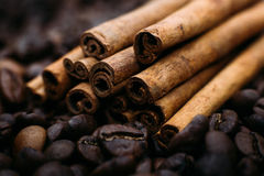 As varas de canela encontram-se em feijões de café perto acima Imagens de Stock