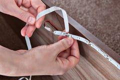 As varas do carpinteiro conduziram a fita dentro da mobília, close-up das mãos imagens de stock