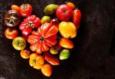 As variedades sortidos de tomates em um coração dão forma Fotografia de Stock Royalty Free