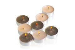 As velas ardentes formam a seta em um fundo branco Imagem de Stock