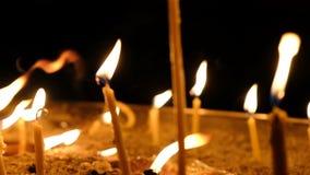 As velas da cera queimam-se na obscuridade na igreja contra o movimento escuro da câmera do close-up do fundo, movimento lento video estoque
