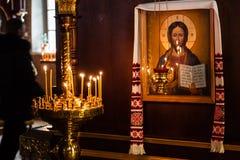 As velas da igreja queimam-se em um castiçal contra o contexto do ico Imagens de Stock
