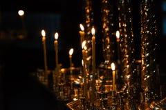 As velas da igreja queimam-se em um castiçal contra o contexto do ico Imagens de Stock Royalty Free