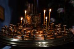 As velas da igreja queimam-se em um castiçal contra o contexto do ico Fotografia de Stock