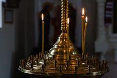 As velas da igreja queimam-se em um castiçal contra o contexto do ico Fotografia de Stock Royalty Free