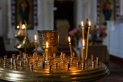 As velas da igreja queimam-se em um castiçal contra o contexto do ico Foto de Stock Royalty Free