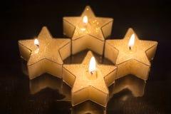 As velas dadas forma de quatro estrelas foram iluminadas para o quarto advento fotos de stock
