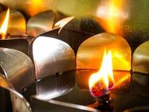 As velas iluminam-se nos frascos inoxidáveis fotografia de stock