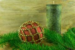 As velas verdes com bolas do Natal e o abeto ramificam em uma placa rústica Fotos de Stock Royalty Free