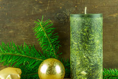 As velas verdes com bolas do Natal e o abeto ramificam em uma placa rústica Imagens de Stock Royalty Free