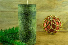 As velas verdes com bolas do Natal e o abeto ramificam em uma placa rústica Foto de Stock
