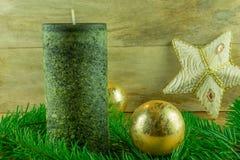 - As velas verdes com bolas do Natal e o abeto ramificam em uma placa rústica Fotografia de Stock