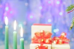 As velas verdes do Natal estão queimando-se Em um fundo azul Fotos de Stock