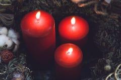 As velas vermelhas em um pinho envolvem-se com decorações Fotos de Stock Royalty Free
