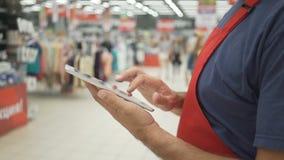 As vendas clerk no avental vermelho usando uma tabuleta digital com a loja no fundo vídeos de arquivo