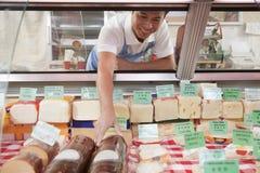 As vendas Clerk o alcance dentro para obter o queijo no supermercado fino contrário foto de stock royalty free