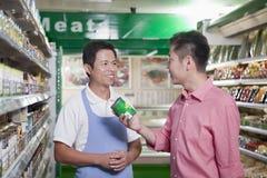 As vendas clerk o sorriso e a ajuda do homem no supermercado, Pequim fotografia de stock
