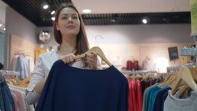 As vendas da compra, mulher atrativa escolhem e tentam a roupa nova na frente do espelho na loja da forma durante descontos dentr video estoque