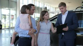 As vendas do carro, gerente atrativo vendem o automóvel aos visitantes, família feliz video estoque