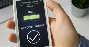 As verificações do homem carregam ao nível de seu carro bonde A bateria é carregada Aplicação de utilização de controle remoto do video estoque