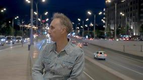 As verificações do homem olham olhares em conduzir automóveis contra a cidade da noite vídeos de arquivo