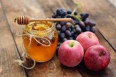 As vespas voam em torno do frasco com mel, uvas e maçãs foto de stock royalty free