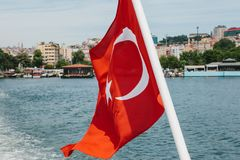 As vibrações turcas nacionais da bandeira no vento contra o contexto do Bosphorus e da Istambul borrados no fotos de stock royalty free