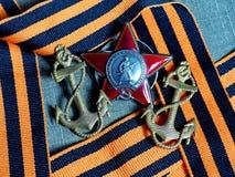 As vigas do close up a âncora do marinheiro 'de um marinheiro ', orden 'de Red Star 'na fita de St George Concessões do soldado h foto de stock