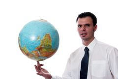 As the World Turns. Young businessman spinning the world on his finger Stock Image
