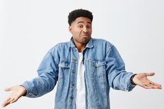 As you say, bro. No problem. Isolated on white portrait of funny dark-skinned man in white t-shirt and denim jacket. Spreading hands with unsure face expression Stock Image