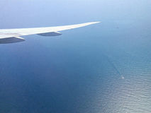 Asa de aviões acima do mar calmo com selagem imóvel da água e dos navios Imagem de Stock Royalty Free