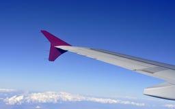 Asa de aviões que voa sobre nuvens, asa de aviões no cloudscape e o céu azul Fotos de Stock