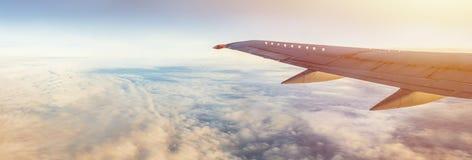 Asa de aviões sob a terra e as nuvens Voo no céu imagem de stock royalty free