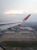 A asa de aviões vê o aeroporto e o plano com pingo de chuva Fotografia de Stock