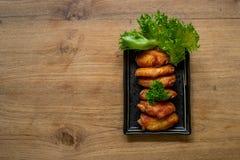 Asa de galinha Nova Orleães saboroso no prato quadrado e na tabela de madeira, T Imagens de Stock